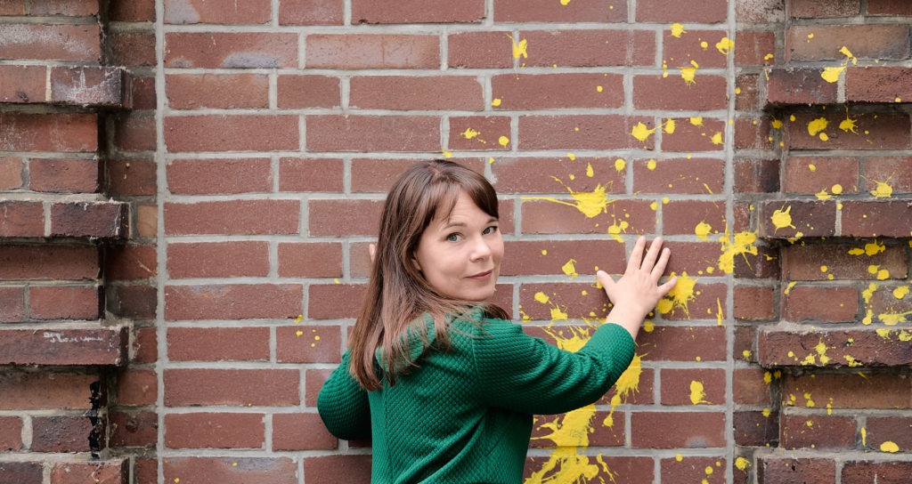 Frau hält Hände an Mauer